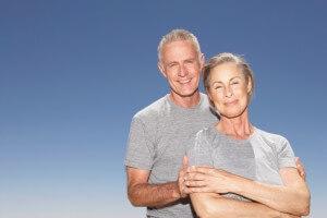 Mature Couple in gray tshirts smiling at camera